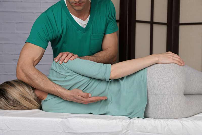 Image of a chiropractor adjusting a patient's back
