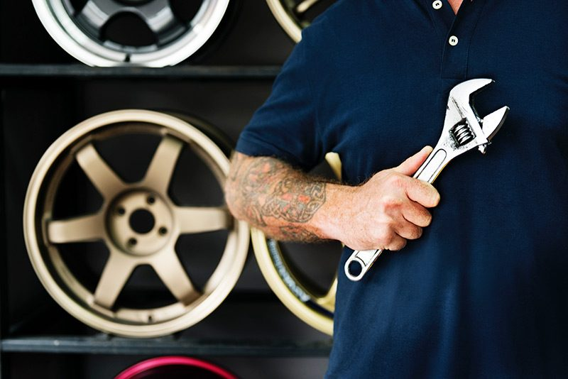 Closeup torso image of man holding wrench with tire rims in background